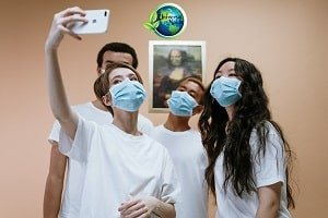 people wearing masks taking a selfie.