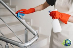 woman cleaning the metal surface with cleaning supplies