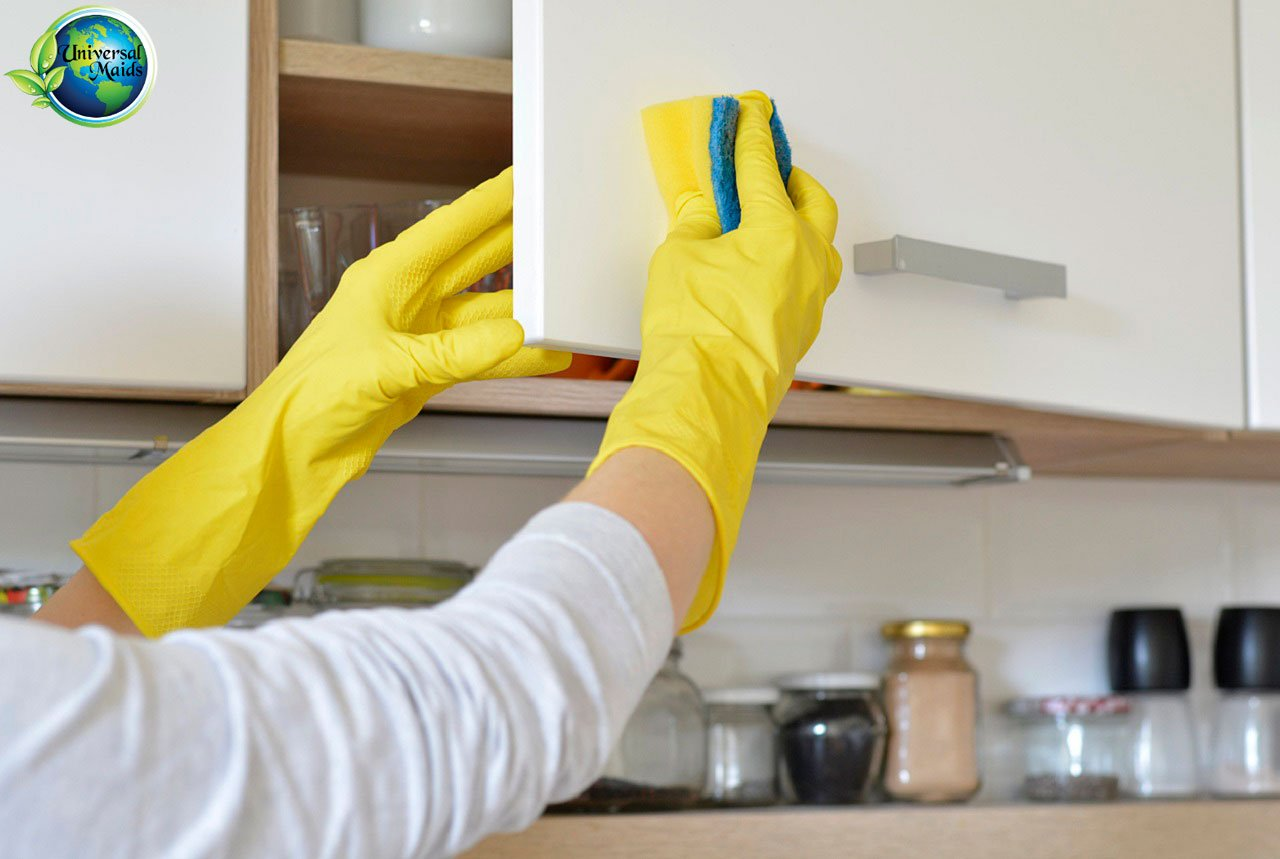 A maid is cleaning the Cabinets